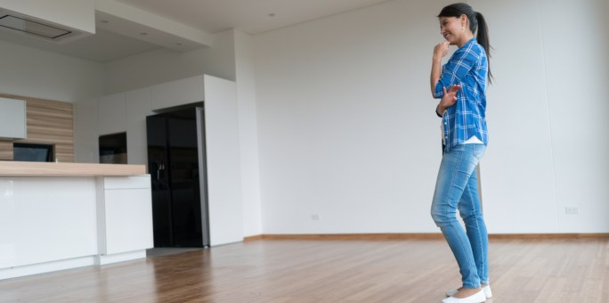 Thoughtful woman at an empty apartment thinking about how to decorate it - real estate concepts