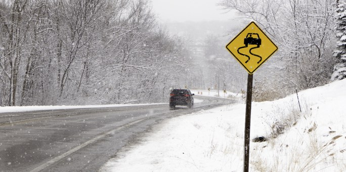 Icy road down hill with slippery when wet sign.