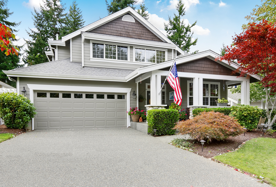 Nice Curb Appeal Of Grey House With Covered Porch And Garage: Nice curb appeal of grey house with garage and driveway. Column porch with American flag. Northwest USA